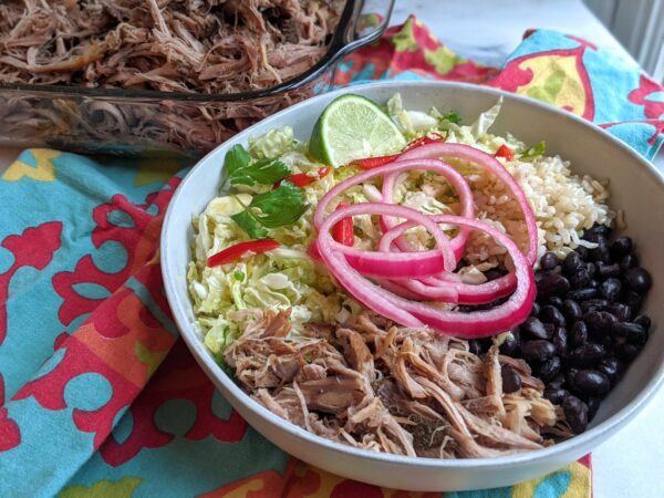 bowl of pork carnitas with sides